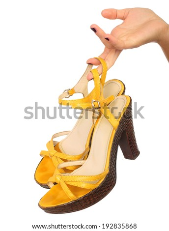 Close up portrait of a female hand holding yellow shoe , isolated background - stock photo