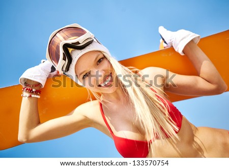 Close-up portrait of a fit girl in bikini holding a snowboard - stock photo