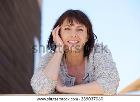 Close up portrait of a fresh natural older woman smiling outdoor - stock photo