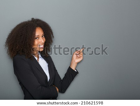 Close up portrait of a friendly business woman pointing finger on gray background - stock photo
