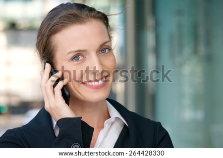 Close up portrait of a friendly business woman smiling with mobile phone  - stock photo