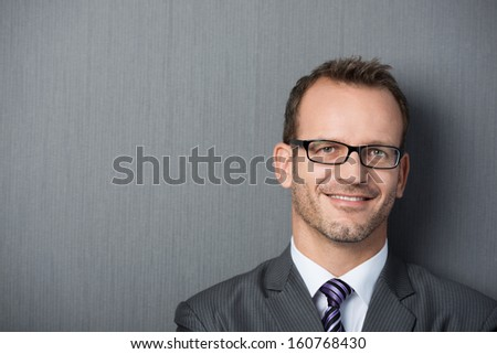 Close-up portrait of a friendly businessman leaning against a gray wall with copy-space on the left - stock photo