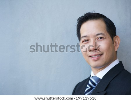 Close up portrait of a friendly businessman smiling on gray background - stock photo