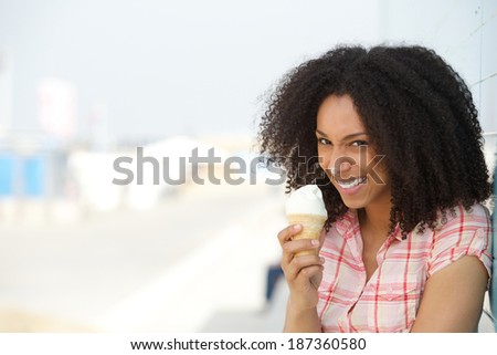 Close up portrait of a fun young woman with ice cream on nose - stock photo