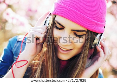 Close up portrait of a funny young swag girl on lush garden listening to music in earphones from smart phone mp3 player. Outdoors, lifestyle. Photo toned style Instagram filters - stock photo