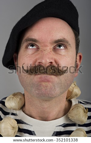 Close up portrait of a garlic seller looking up to the heavens. He has an annoyed expression.  - stock photo