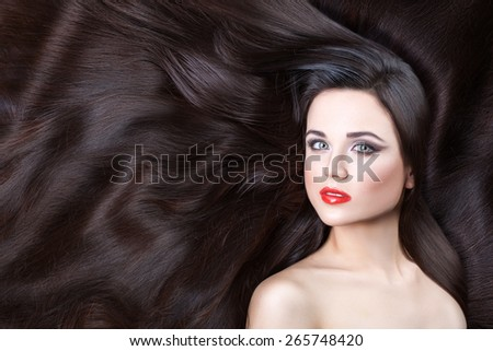 Close-up portrait of a girl. Brunette girl. She is lying on his wavy hair. - stock photo