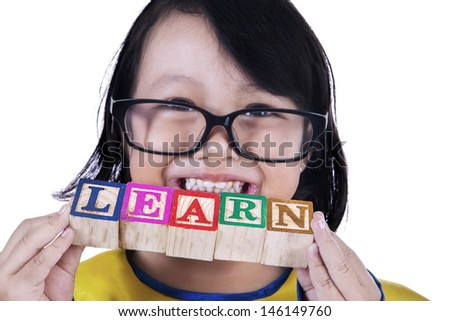 Close-up portrait of a girl holding LEARN wooden cube toy on white