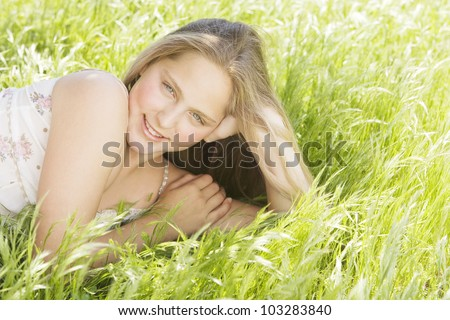Close up portrait of a girl in a field of green grass, smiling under a golden light. - stock photo