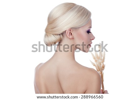 Close-up portrait of a girl in profile. She's blonde, her hair arranged in a hairstyle. - stock photo