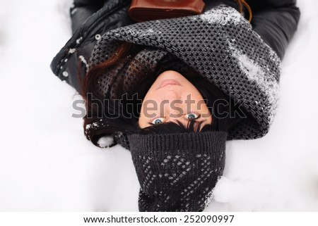 Close up portrait of a girl lying in the snow