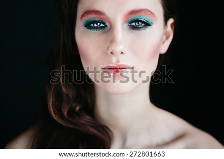 Close up portrait of a girl on a dark background with bright makeup