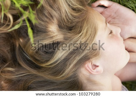 Close up portrait of a girl sleeping in a garden with her hair spreading behind her. - stock photo