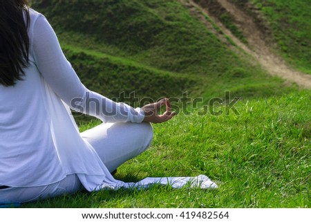 Close-up portrait of a girl who is sitting in the lotus position. Wind waves her hair and white clothes. Concept: relaxation, harmony and health.