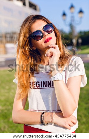 Close-up portrait of a girl with ombre hair holding her left hand near chin. Girl wears white shirt and red skirt. Girl stands in park in the citycenter. She wears black sunglasses. - stock photo