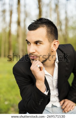 Close-up portrait of a good looking beautiful young man in costume outdoors. - stock photo