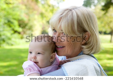 Close up portrait of a grandmother holding granddaughter outdoors - stock photo
