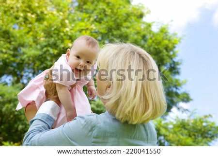 Close up portrait of a grandmother lifting grandchild up - stock photo