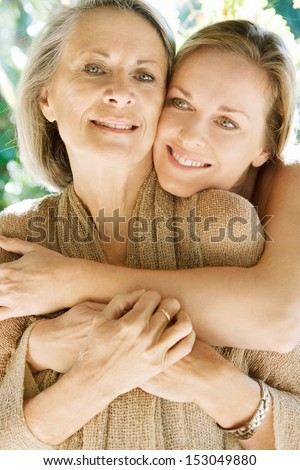 Close up portrait of a grown daughter and her mature mother hugging and loving each other during a sunny day in a home garden, being together and smiling outdoors. - stock photo