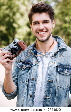 Close-up portrait of a handsome hipster guy holding camera outdoors in the park