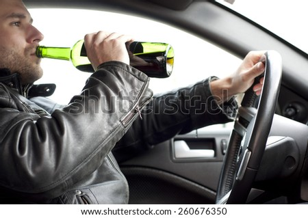 Close up portrait of a handsome man drinking alcohol while driving a car, do not drink and drive concept - stock photo
