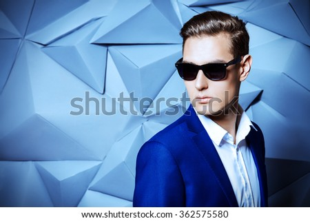Close-up portrait of a handsome man in elegant classic suit and sunglasses. Men's beauty, fashion. - stock photo
