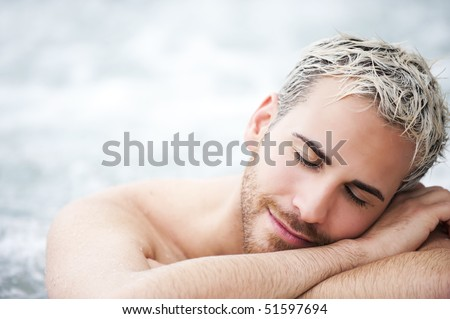 Close up portrait of a handsome man in jacuzzi with closed eyes - stock photo