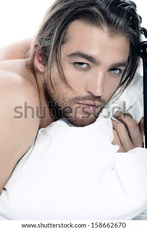 Close-up portrait of a handsome man lying in a bed. Isolated over white. - stock photo