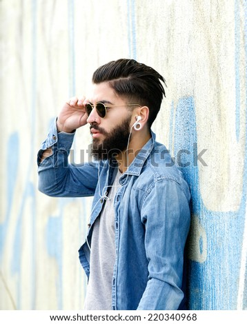 Close up portrait of a handsome man with beard listening to music with earphones - stock photo