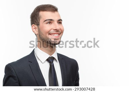 Close up portrait of a handsome young bearded man wearing a formal black suit looking aside and smiling happily, isolated on white background