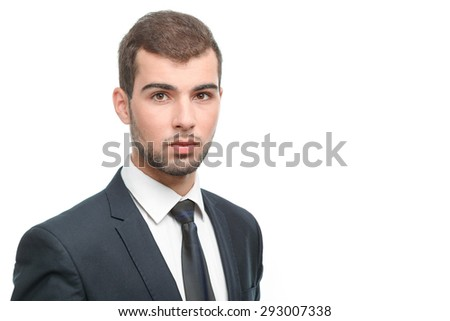 Close up portrait of a handsome young bearded man wearing a formal black suit standing looking serious, isolated on white background - stock photo