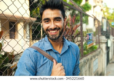 Close up portrait of a handsome young Indian man smiling  - stock photo