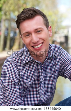 Close up portrait of a handsome young man relaxing outdoors - stock photo
