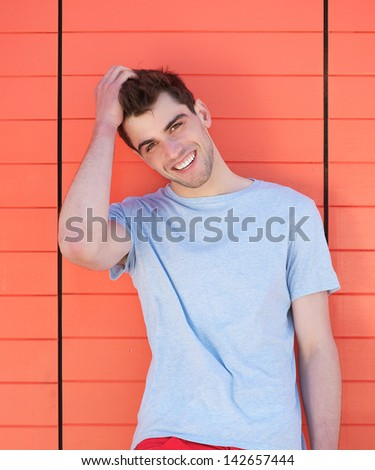 Close up portrait of a handsome young man smiling with hand in hair, outdoors - stock photo