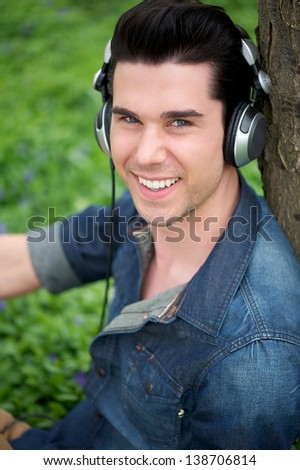 Close up portrait of a handsome young man smiling with headphones - stock photo