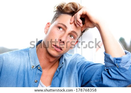 Close up portrait of a handsome young man thinking - stock photo