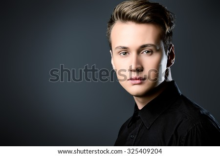 Close-up portrait of a handsome young man thoughtfully looking at the camera. Studio shot. Men's beauty, fashion. - stock photo