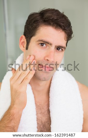 Close up portrait of a handsome young man touching his face