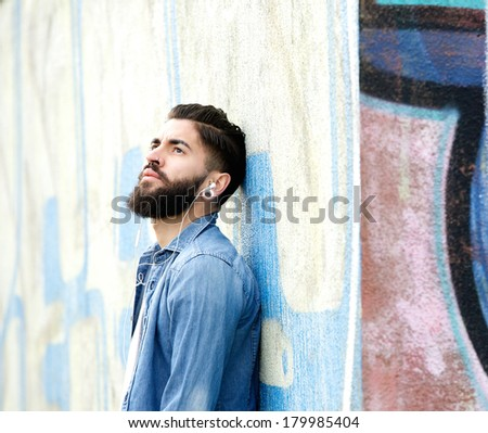 Close up portrait of a handsome young man with beard listening to music on earphones outdoors - stock photo