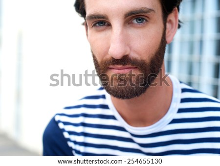 Close up portrait of a handsome young man with beard staring - stock photo