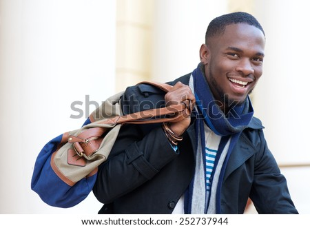 Close up portrait of a happy african american man standing outdoors with bag - stock photo