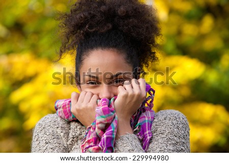 Close up portrait of a happy african american woman posing with sweater and scarf - stock photo