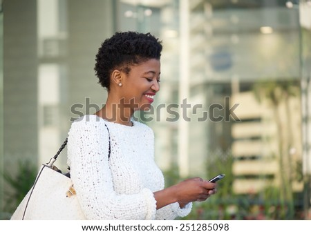 Close up portrait of a happy african american woman reading text message on mobile phone - stock photo
