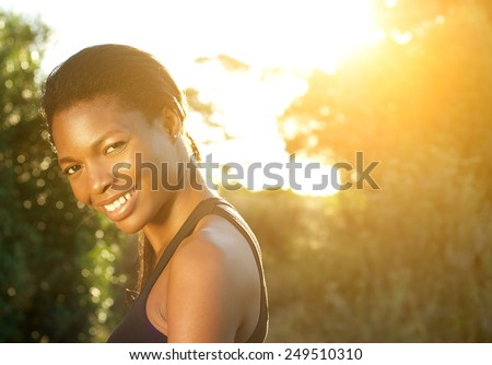 Close up portrait of a happy african american woman smiling outdoors - stock photo