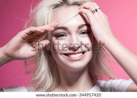 Close-up portrait of a happy blonde woman on the pink background - stock photo