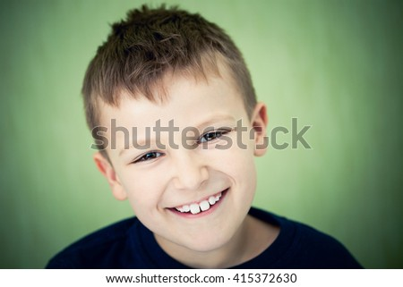 Close up portrait of a happy boy smiling on a green background. - stock photo