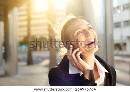 Close up portrait of a happy business woman laughing on mobile phone outside - stock photo