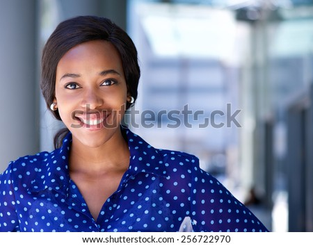 Close up portrait of a happy business woman smiling outside office building - stock photo