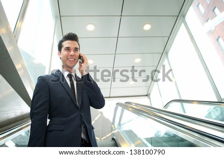 Close up portrait of a happy businessman talking on the phone on escalator - stock photo