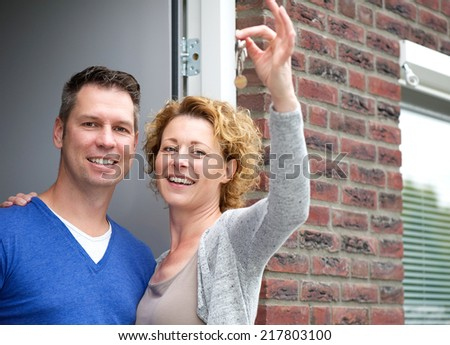Close up portrait of a happy couple holding keys to their new home - stock photo
